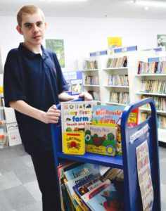 student librarian with book trolley