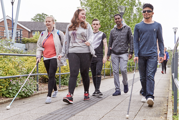 Image of young people with visual impairment walking with sticks.