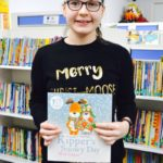 Student in Christmas jumper in a library