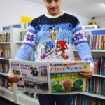 Student in Christmas jumper reading first news