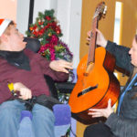student in wheelchair with guitar and teacher