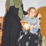 student in wheelchair playing tamborine