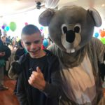 Young man with mascot at the Albany Taxi charity party