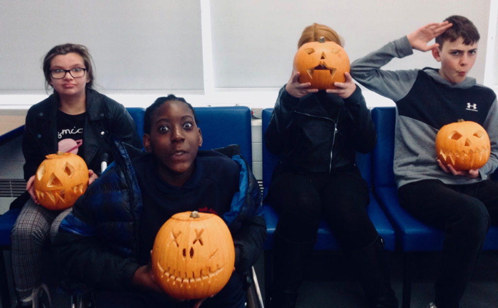 Four children holding carved pumpkins