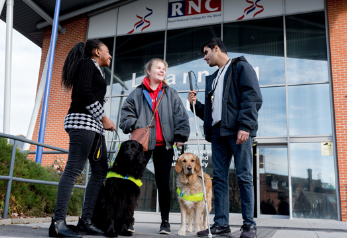 YOung people with guide dogs outside college