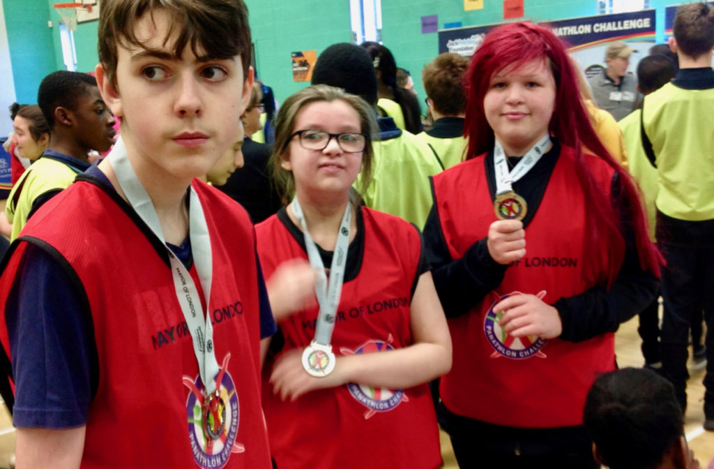 three children with silver medals