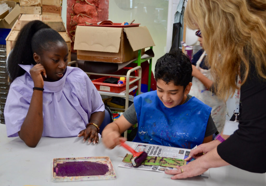 Child printing with teacher and support