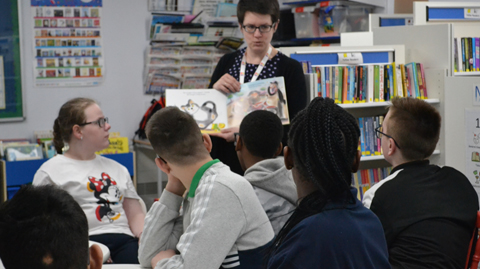 Teacher holding up book to class