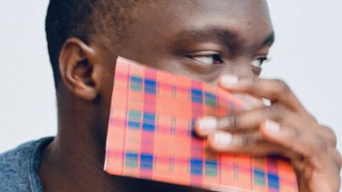Boy's eye above a piece of tartan