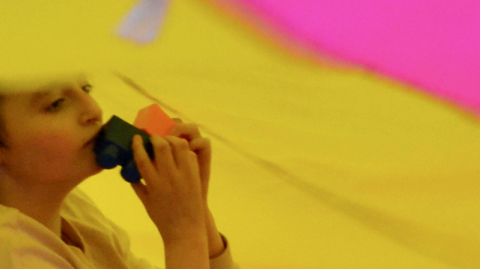 Girl under colourful parachute