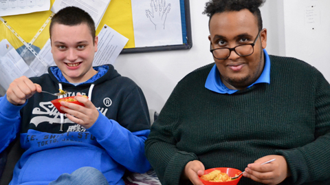 Two young men sitting, smiling and about to eat