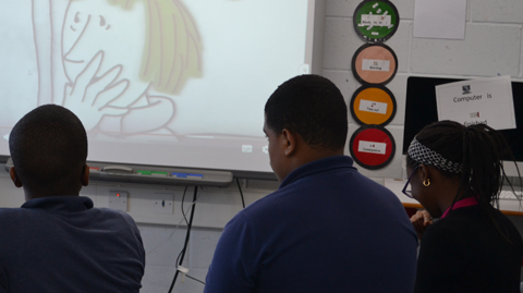 Three backs of head of students looking at a white board