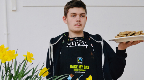 Young man holding plate of Welsh cakes