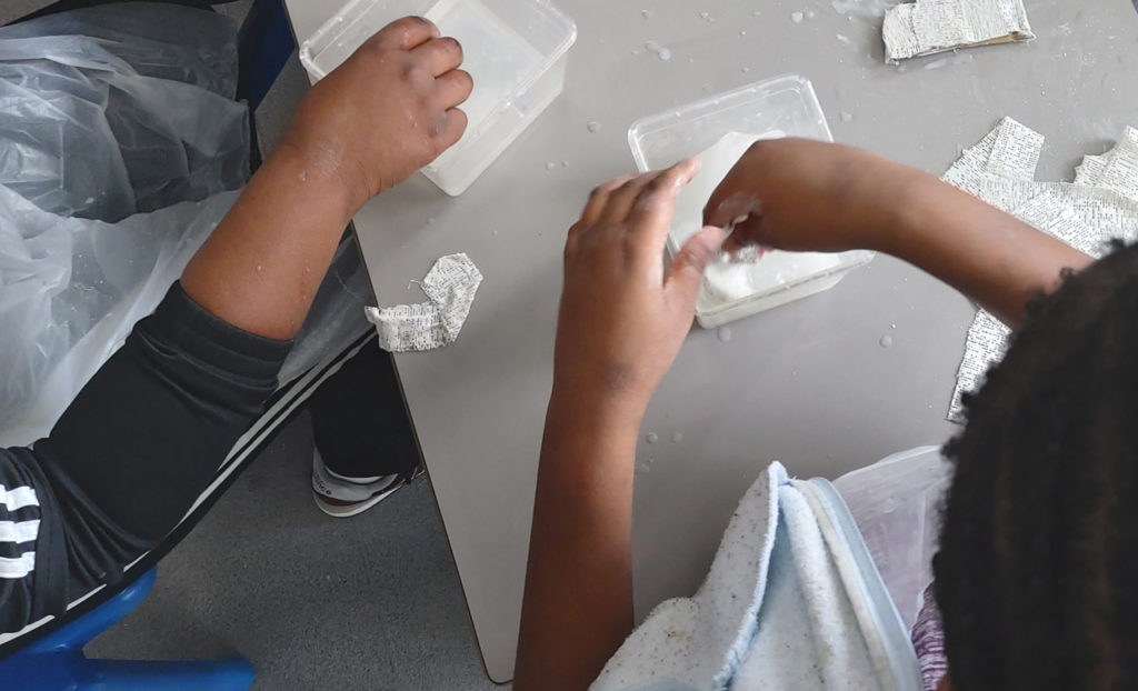 Children's hands in a plaster mixture