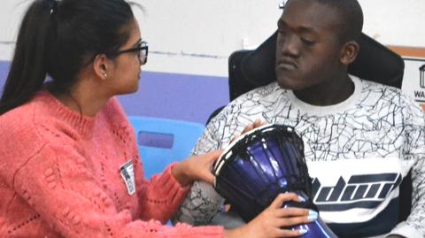 Boy with teacher showing him a drum