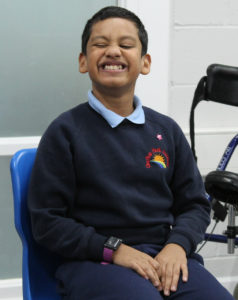 A boy smiling in a classroom with a walker in the background