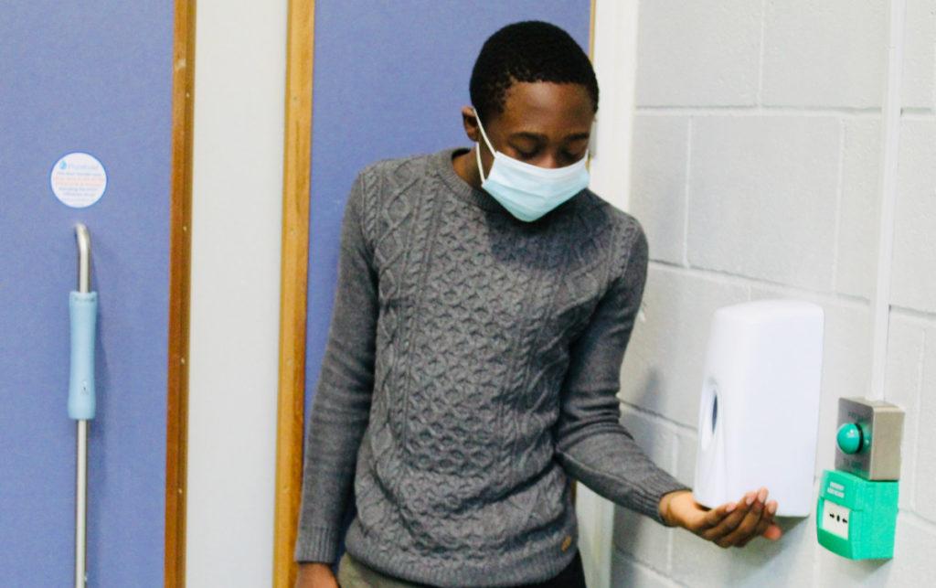 Child using hand sanitiser