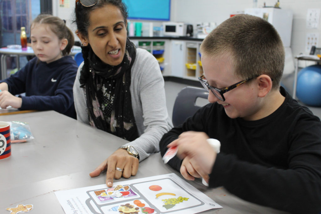 Teacher and student at desk looking at healthy eating symbols