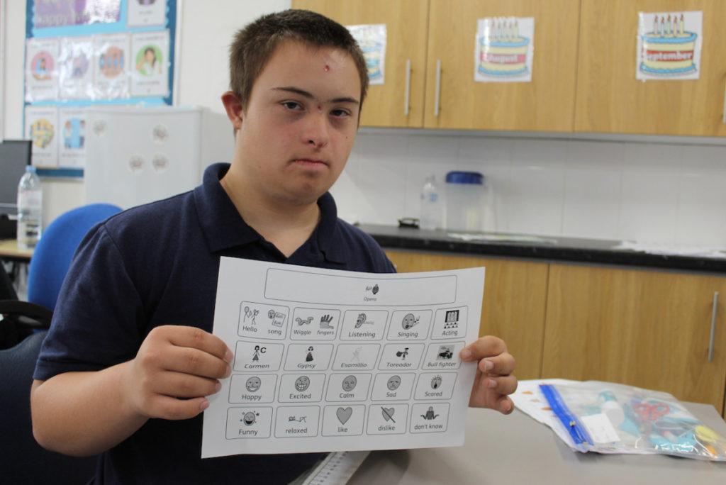 Boy holding a sheet of symbols