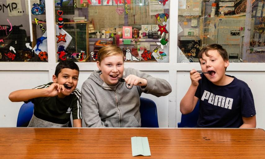 Image of three boys at a table