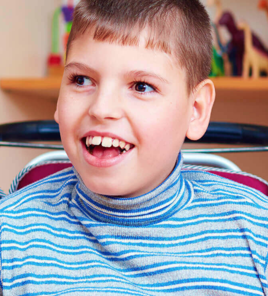 Image of a boy smiling and showing his teeth.